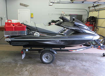 side view of jetski loaded with extra gas cans and coolers