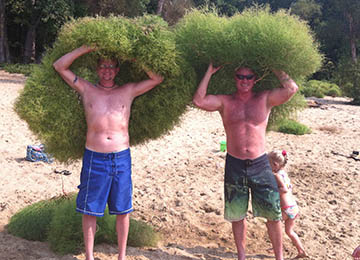 two guys holding seaweed over their heads width=